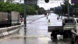 ขับขี่รถจักรยานยนต์ในถนนน้ำท่วมของประเทศไทย
