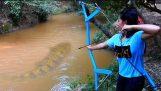 Ένα κορίτσι κατασκευάζει τόξο από πλαστικούς σωλήνες και ψαρεύει