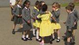 A little girl shows new artificial leg to classmates
