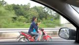 Mother on motorcycle is texting while driving