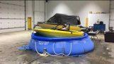 Två berusade män segla med en liten båt på ytan av en uppblåsbar pool