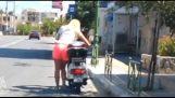 Donna, cercando di ottenere di fronte a uno scooter con il cavalletto