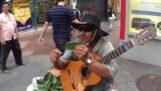 Sokak müzisyeni bir levha ile bir trompet sesini taklit eder
